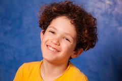 Preteen curly boy smiling and looking at camera. Close-up portrait of preteen curly boy smiling and looking at camera Stock Photo