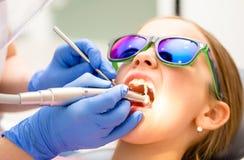Preteen flicka som mottar tandlokalvårdtillvägagångssätt i pediatrisk tand- klinik royaltyfri fotografi