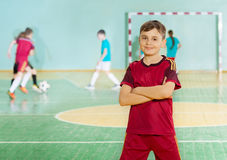 Preteen football player standing in sports hall Royalty Free Stock Photography