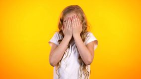 Preteen frightened girl covering face with palms, childish fears unexpected news. Stock photo stock photography