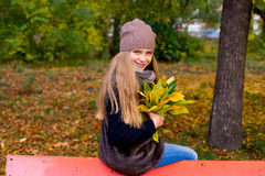 Preteen girl in autumn park with leafs Royalty Free Stock Photos