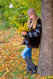 Preteen girl in autumn park with leafs Royalty Free Stock Image
