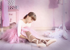 Preteen girl in ballet class hall put on pointe stock image