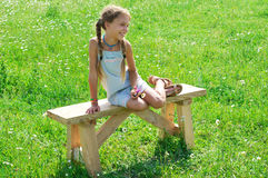 Preteen girl on bench in grass Royalty Free Stock Photography