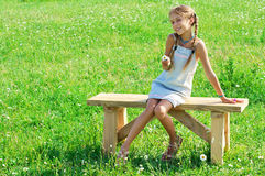 Preteen girl on bench in grass Stock Photo