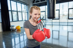 Preteen girl in boxing gloves with sport bottle. Royalty Free Stock Images