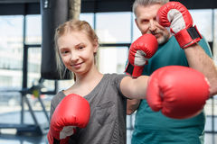 Preteen girl boxing with senior trainer Royalty Free Stock Photos
