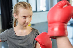 Preteen girl boxing with trainer Stock Images