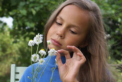 Preteen girl with daisy Stock Images
