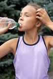 Preteen girl drinking watter Stock Images