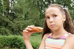 Preteen girl eats bread Royalty Free Stock Photos