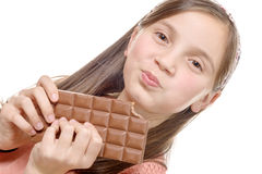 Preteen  girl eats chocolate, isolated on white Royalty Free Stock Images