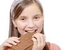 Preteen  girl eats chocolate, isolated on white Stock Image