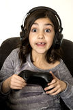 Preteen girl with eyes wide open playing video game excited Royalty Free Stock Photography