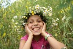 Preteen girl in garland. Cheerful preteen girl in fild flower garland on green grass background Stock Photos