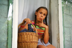 Preteen girl with grapes. Preteen girl sitting in window with basket full of grapes Royalty Free Stock Images