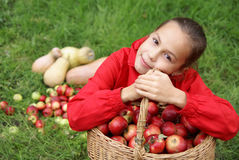 Preteen girl on grass. Preteen girl sits in green grass holding basket of organic apples Stock Photo