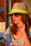 Preteen girl. With hat and sunglasses in sunset light Stock Images