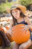 Preteen Girl Holding A Large Pumpkin at the Pumpkin Patch Stock Photo