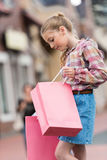 Preteen girl holding pink shopping bags and looking inside one of them Stock Image