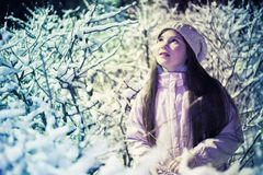 Preteen girl in knitted white hat and jacket. Pretty preteen girl in knitted white hat and jacket on the snow bushes background under street light night scean Royalty Free Stock Image