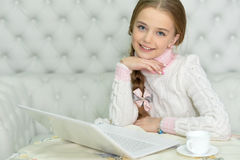 Preteen girl with laptop Stock Image