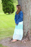 Preteen girl leaning against a tree. A vertical picture of a preteen girl dressed in a long skirt and jean jacket and with bare feet leaning against a tree Royalty Free Stock Photo
