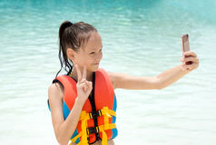 Preteen girl in life vest takes selfie by cell phone camera. Smiling Preteen girl in life vest takes selfie by cell phone camera. Blurred water in background Stock Photos