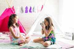 Girl Photographing Her Best Friend During Pajama Party. Preteen girl photographing her best friend during pajama party at home royalty free stock images