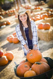 Preteen Girl Playing with a Wheelbarrow at the Pumpkin Patch Royalty Free Stock Images
