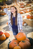 Preteen Girl Playing with a Wheelbarrow at the Pumpkin Patch Stock Images