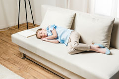 Preteen girl relaxing on sofa with white book Stock Images