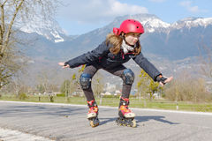 Preteen girl on roller skates in helmet at track. A pretty preteen girl on roller skates in helmet at a track Stock Photos
