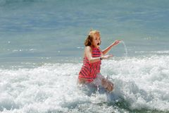 PreTeen Girl Running Out of the Cold Ocean Water Her Mouth is Op royalty free stock photo