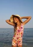 Preteen girl on sea beach. Preteen girl in straw hat enjoying sun-bath on sea beach Royalty Free Stock Photos