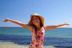 Preteen girl on sea beach. Preteen girl in straw hat enjoying sunbath on sea beach Stock Image