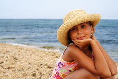 Preteen girl on sea beach. Portrait of cheerful preteen girl in straw hat enjoying sun-bath on sea beach Stock Photography