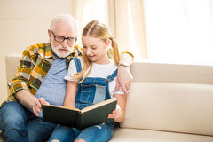 Preteen girl with senior man in eyeglasses reading book together. Smiling preteen girl with senior men in eyeglasses reading book together Stock Image