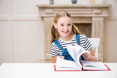 Preteen girl sitting at table with book and smiling at camera Royalty Free Stock Photo