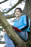 Preteen girl sitting in tree writing Royalty Free Stock Image