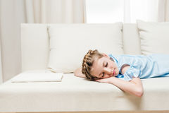 Preteen girl sleeping on sofa with white book Royalty Free Stock Photography