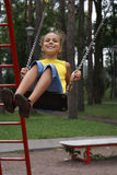 Preteen girl on swing set stock photography