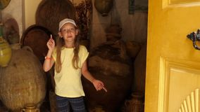 Preteen girl talking about big ancient ceramic jugs in small room stock video