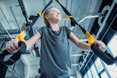 Preteen girl training with resistance bands in fitness class. Gym class kids concept Royalty Free Stock Photography