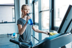 Preteen girl training on treadmill and drinking water in fitness class Stock Photo
