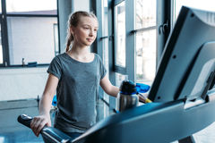 Preteen girl training on treadmill in fitness class Royalty Free Stock Images