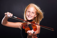 Preteen girl violin. Cheerful preteen girl playing violin on black background Stock Photos