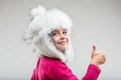 Preteen girl wearing fluffy cap giving thumb up. Portrait of preteen smiling girl wearing fluffy winter cap giving thumb up against plain background Stock Image