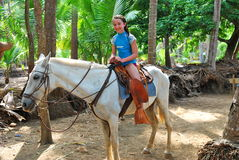 Preteen girl on a white horse in the tropics Stock Photo