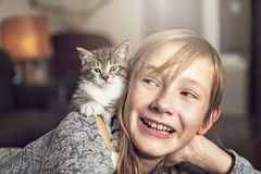 Preteen girl of 10 years old with her cat pet on the sofa stock photo